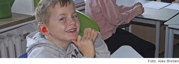 Grundschüler mit Hörgerät sitzt am Tisch im Klassenzimmer und lacht in die Kamera.