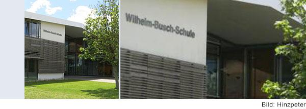 Zweistöckiges Schulhaus, das teilweise mit Holz verkleidet ist. Auf der Wand steht Wilhelm-Busch-Schule.