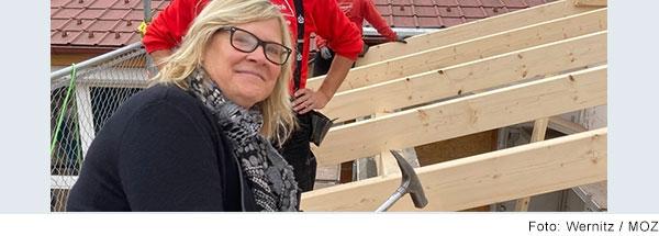 Richtfest. Eine blonde Frau mit dunkler Brille sitzt auf dem neuen Dachstuhl des offenen Dachs. Sie hat einen Hammer in der Hand und lacht in die Kamera. Hinter ihr stehen zwei  Zimmermänner.