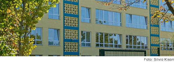 Mehrstöckiges Gebäude mit gelb-blauer Fassade und großen Fenstern.
