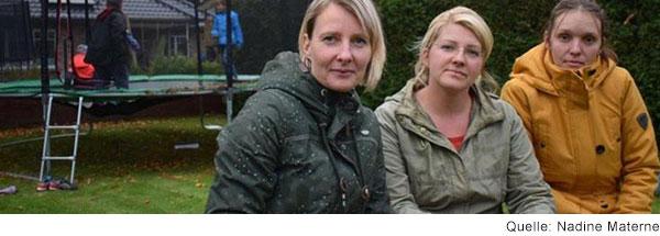 Drei Frauen sitzen nebeneinander auf einem Holzpodest in einem Garten. Sie schauen in die Kamera. Im Hintergrund sieht man drei Kinder auf einem großen Trampolin.