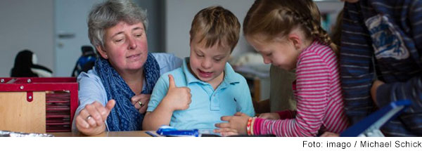 Frau sitzt am Tisch im Klassenzimmer. Auf ihrem Schoß sitzt ein Junge mit Trisomie 21 und spricht. Drei weitere Kinder stehen um sie herum. Alle schauen auf sein Heft.
