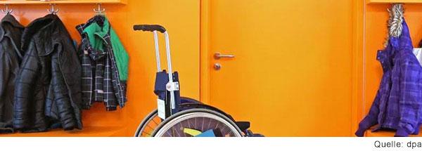 Ein leerer Rollstuhl steht im Schulflur vor der Tür zum Klassenzimmer.
