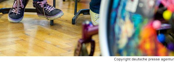Blick unter den Tisch in einem Klassenzimmer. Man sieht die Füße von mehreren Kindern auf einem Stuhl. Ein Kind sitzt im Rollstuhl.
