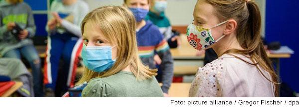 Blick in ein Klassenzimmern mit Kindern. Im Vordergrund sitzen zwei Mädchen mit dem Rücken zu Kamera. Sie tragen Masken. Eines der Mädchen dreht sich um und schaut und die Kamera.