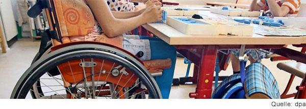 Drei Kinder arbeiten an einem Tisch im Klassenzimmer. Ein Kind sitzt im Rollstuhl.
