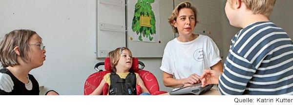 Eine Frau und drei Kinder mit unterschiedlichen Behinderungen sitzen um einen Tisch und arbeiten.