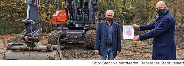 Zwei Männer mit Mundschutz stehen vor einem Bagger, einer der beiden hält die Baugenehmigung in die Kamera.