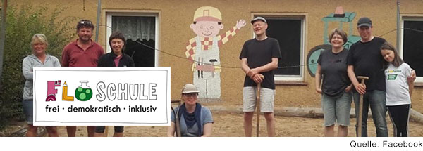 Acht Menschen stehen lachend vor einem Gebäude, auf dessen Wand ein Bauarbeiter und ein Traktor gemalt ist. Einige haben Spaten in der Hand.