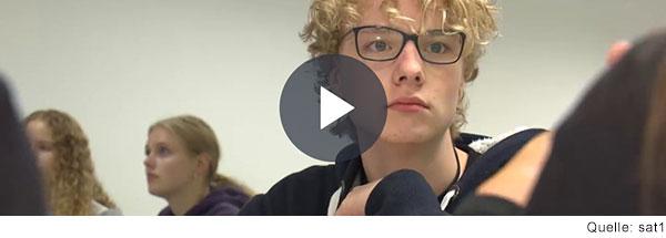 Jugendlicher mit blonden Haaren und dunkler Brille schaut in die Kamera