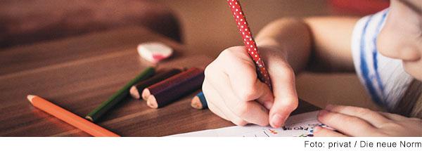 Grundschulkind sitzt am Tisch und schreibt