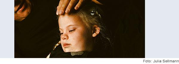 Eine erwachsene Person legt einem Mädchen mit Down-Syndrom die Hand auf den Kopf.