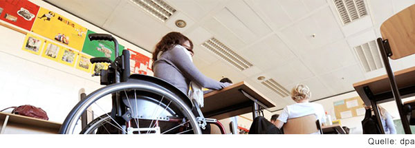 Junge Frau sitzt am Tisch im Klassenzimmer und arbeitet. Sie sitzt im Rollstuhl.