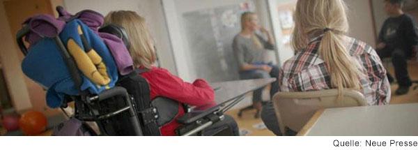 Kind im elektrischen Rollstuhl sitzt im Unterricht.