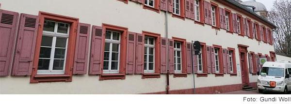 Zweistöckiges Gebäude mit roten Fensterläden.
