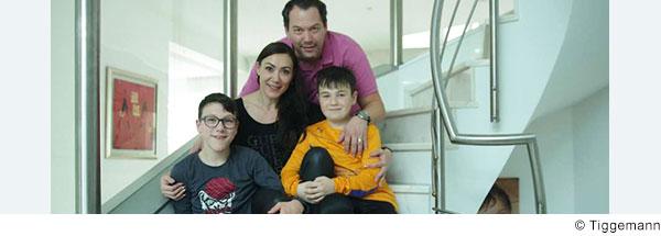 Vater Mutter und zwei jugendliche Jungs sitzen zusammen auf einer Treppe und lächeln in die Kamera.
