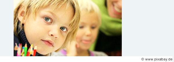 Blonder Junge im Grundschulalter schaut interessiert in die Kamera. Im Hintergrund sieht an weitere Kinder.