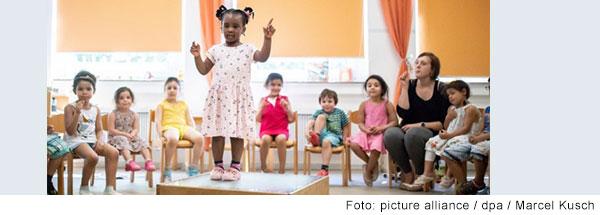 Mädchen im Grundschulalter steht auf einem Podest in der Mitte eines Stuhlkreises mit weiteren Kindern. Sie macht Gebärden vor. Die anderen machen mit.