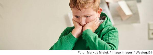 Junge sitzt am Schreibtisch, den Kopf auf die Hände gestützt und schaut nachdenklich nach unten.