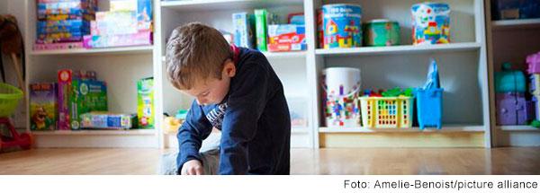 Junge sitzt am Boden und macht ein Puzzle