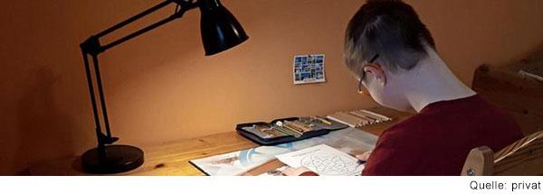 Junge sitzt am Schreibtisch und arbeitet