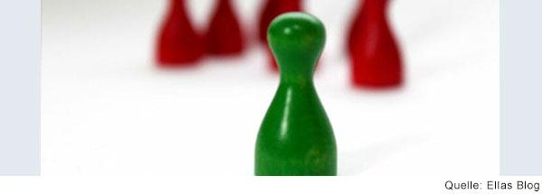 Eine einzelne grüne Spielfigur steht im Vordergrund. Im Hintergrund sind mehrer rote Figuren zu sehen.