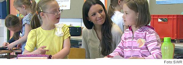 Lehrerin sitzt im Klassenzimmer zwischen zwei Schülerinnen und spricht mit Ihnen.