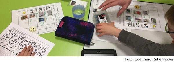 Kinder arbeiten an einem Tisch mit unterschiedlichen Lehrmaterialien
