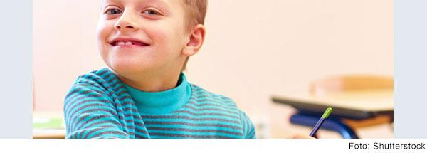 Junge sitzt im Klassenzimmer und lacht in die Kamera