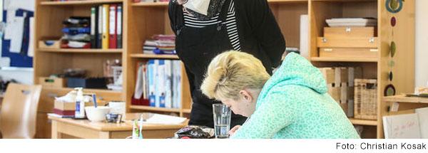 Schülerin sitzt im Klassenzimmer und schreibt, Frau steht neben ihr schaut ihr zu.