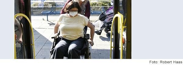 Eine Frau hilft einer Frau mit dem Rollstuhl in einen Bus zu kommen.