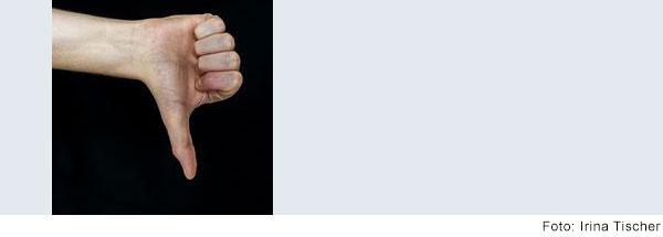 Hand vor schwarzem Hintergrund. Daumen zeigt nach unten.