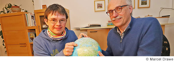 Mann mit grauen Haaren und Brille sitzt neben Jugendlichem mit Down-Syndrom an einem Tisch. Sie halten einen Globus in ihrer Hand und lachen in die Kamera.