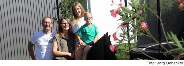 Ein blonder Junge mit Down-Syndrom im Grundschulalter sitzt auf einem Holzpferd. Hinter ihm sitzt ein älteres Mädchen mit langen blonden Haaren. Neben den beiden stehen eine Frau und ein Mann.
