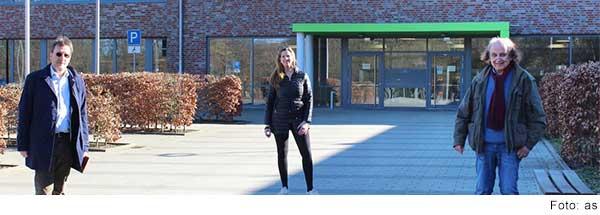 Eine Frau und zwei Männer stehen mit großem Abstand zueinander vor einen großen Gebäude mit Klinker-Fassade.