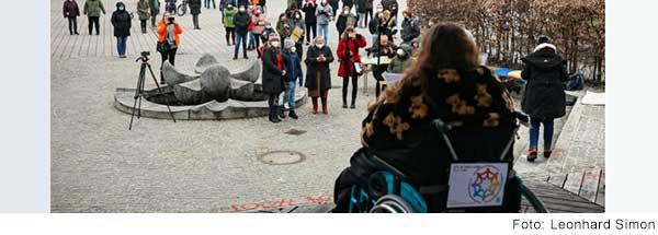Blick in einen Hof mit Menschen. Im Vordergrund sitzt eine Frau im Rollstuhl mit dem Rücken zur Kamera.