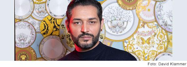 Ein Mann mit dunklem Haar und akkurat geschnittenem kurzen dunklen Vollbart schaut ernst in die Kamera.