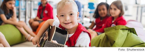 Ein blonder Junge mit Down-Syndrom im Grundschulalter spielt auf einer sehr großen Gitarre udn lacht in die Kamera. Hinter ihm sind mehrere Kinder. Sie schauen ihn freundlich lächelnd an.