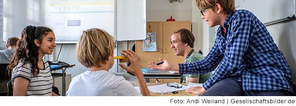 Blick in eine Klassenzimmer. Im Vordergrund sitzt ein Junge auf einem Tisch. Er streckt einem Mädchen die Hand entgegen. Beide lachen. Ein blonder Junge schaut Ihnen zu.
