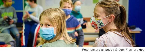 Blick in ein Klassenzimmer mit vielen Kindern. Alle tragen einen Mund-Nasenschutz. Im Vordergrund sitzen zwei Mädchen mit dem Rücken zur Kamera. Eines der beiden, mit blonden mittellangen Haaren, dreht sich um und schaut in die Kamera.