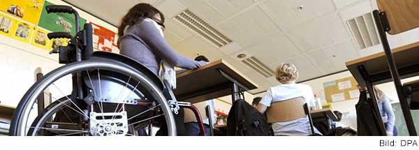 Blick in ein Klassenzimmer mit Jugendlichen. Im Vordergrund sitzt eine junge Frau im Rollstuhl am Tisch.
