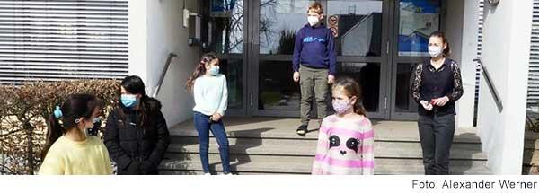 Auf einer Treppe vor dem Eingang eines Gebäudes stehen eine Frau und 5 Kinder mit Abstand. Alle tragen einen Mund-Nasenschutz.