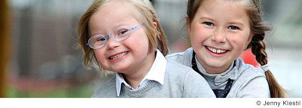 Zwei Mädchen im Grundschulalter umarmen sich und lachen. Eines der Mädchen hat Down-Syndrom.