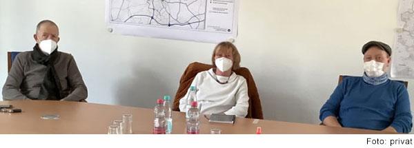 Eine Frau und zwai Männer mit Mund-Nasen-Schutz sitzen an einem Tisch.