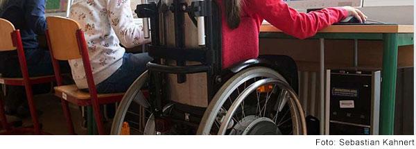 Mehrere Kinder sitzen im Klassenzimmer einem Tisch und arbeiten. Eines der Kinder sitzt im Rollstuhl.