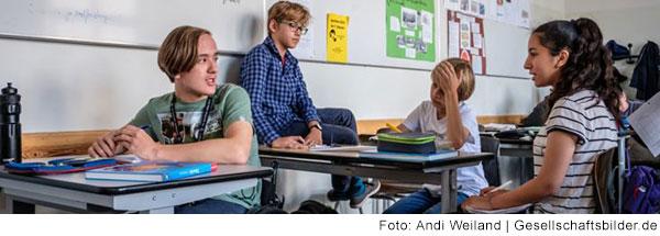 Schüler und Schülerinnen im Klassenzimmer sprechen miteinander.