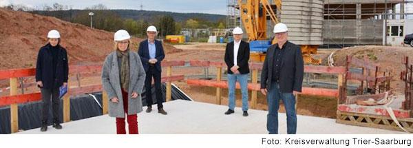 Fünf Menschen mit weißen Helmen stehen auf einer Baustelle und lachen in die Kamera