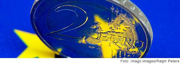 Zwei-Euro-Münze steht auf einem leuchtend blauen Grund mit gelben Sternen.