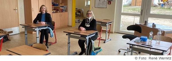 Zwei Frauen sitzen mit Mund-NAsen-Schutz in einemleeren Klassenzimmer an Tischen und lachen in die Kamera.