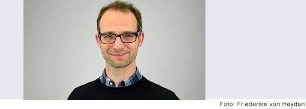Junger Mann mit kurzen braunen Haaren und dunkler Brille lächelt in die Kamera